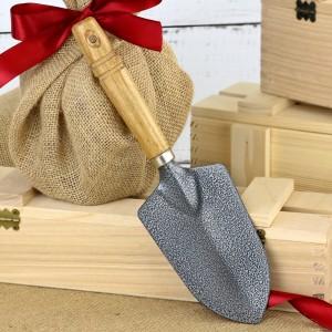 drzewko w drewnianej skrzyni z łopatką na prezent
