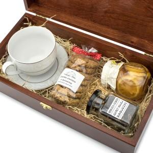 drewniana skrzynka z filiżanką, herbatą, ciastami i syropem na prezent dla teścia na imieniny